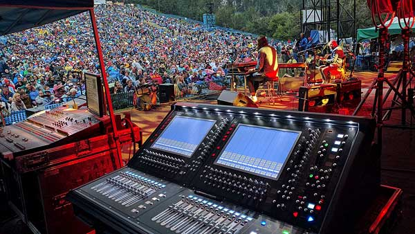 Allstar Show Industries Audio Production Services at the Edmonton Folk Music Festival looking out across one of the mixing consoles at the crowd from the on stage monitor position