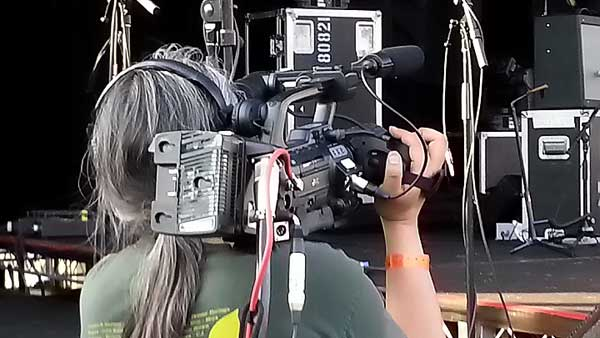 A camera operator on the Allstar Show Industries video crew at an outdoor music festival